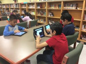 students coding in library,