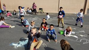 Students drawing with chalk outside.