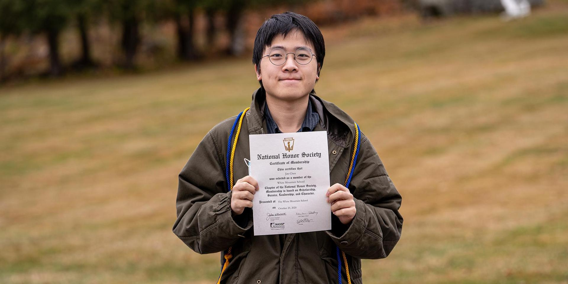 A student wearing his NHS cords and proudly showing off his NHS certificate.
