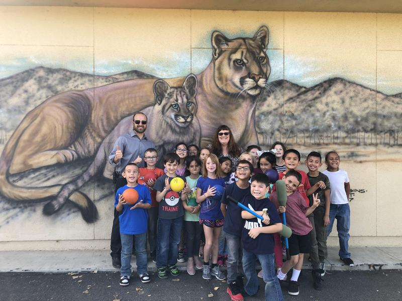 Principal Daniel Betts, Counselor Amanda Niaves, and students in front of the Cottonwood cougar mural.