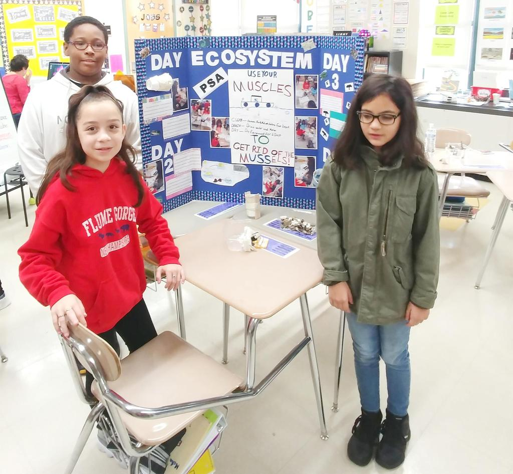 Three Keverian fifth graders stand in front of the public service announcement they created for a project entitled 'The Mystery of Loon Lake'