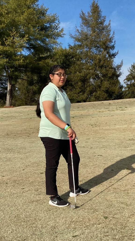 a picture of a girl playing golf