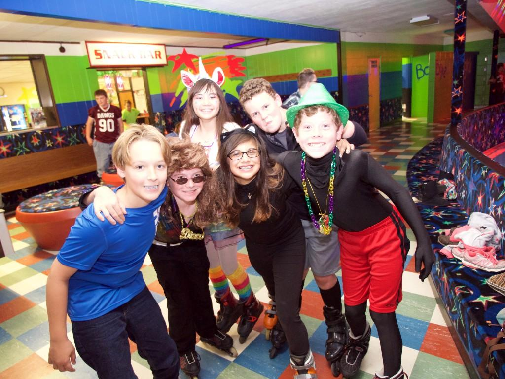 kids pose in Halloween outfits at roller rink