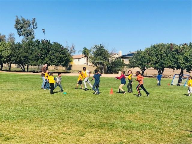Students and teacher running, playing ball on field