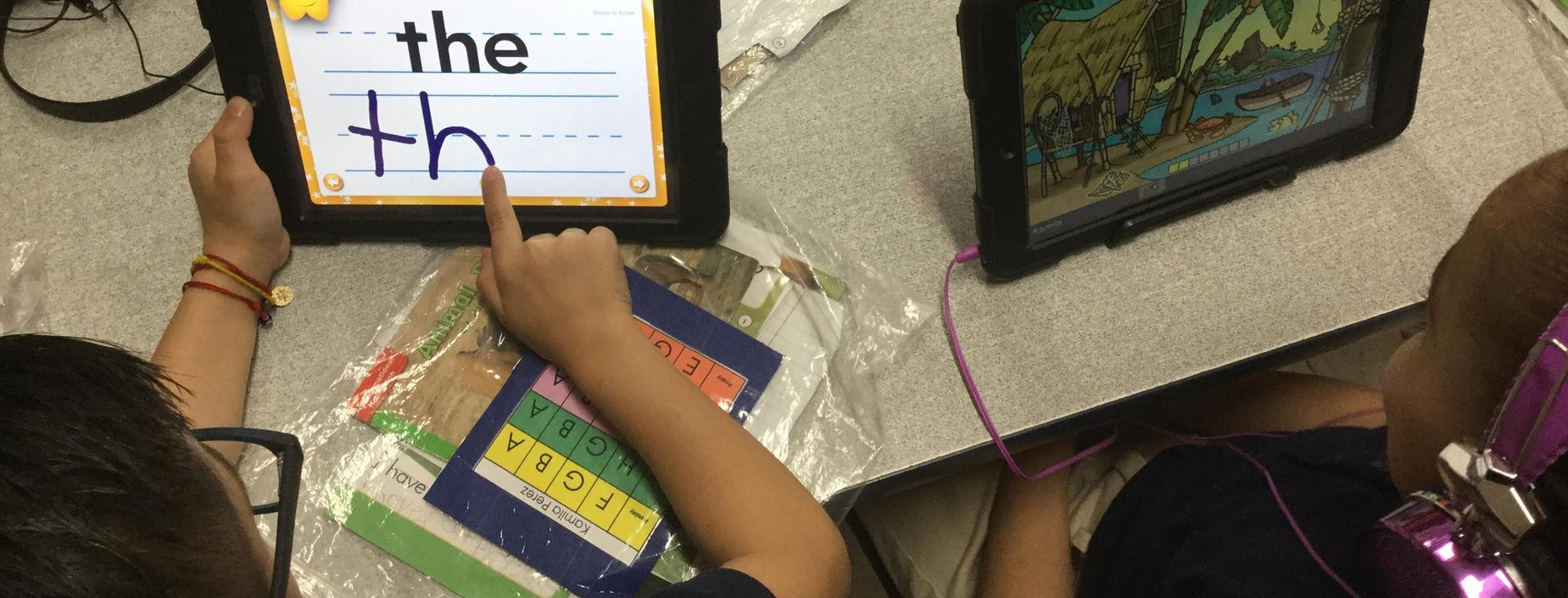2 students using iPads for learning activities.