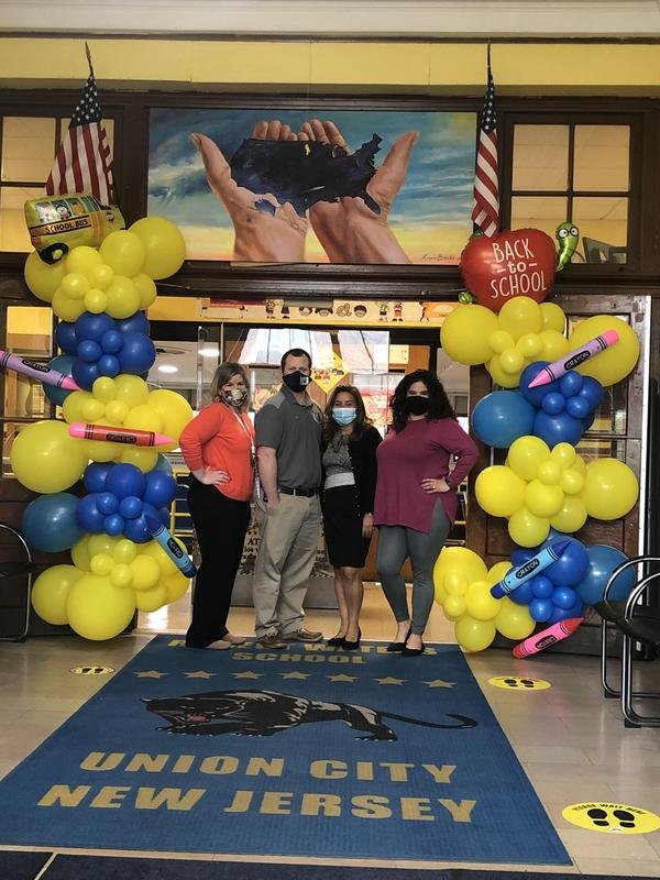 Administration posing between yellow and blue balloon decorations