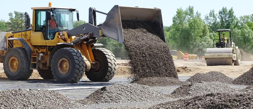 This is a picture of a front loader placing stone June 24, 2019 s an early step in the process of re-constructing pickleball-tennis courts on the athletic fields segment of the main campus.