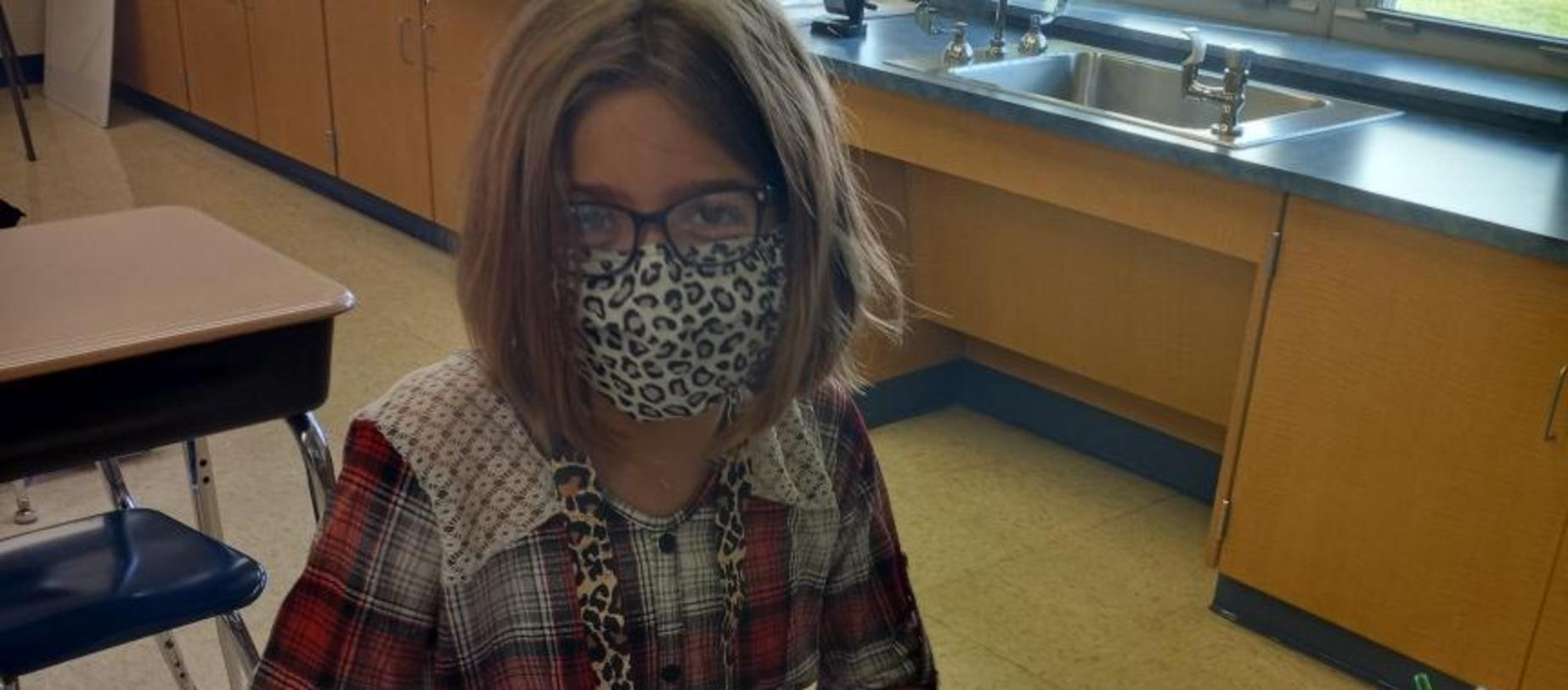 girl wearing a mask working at her desk