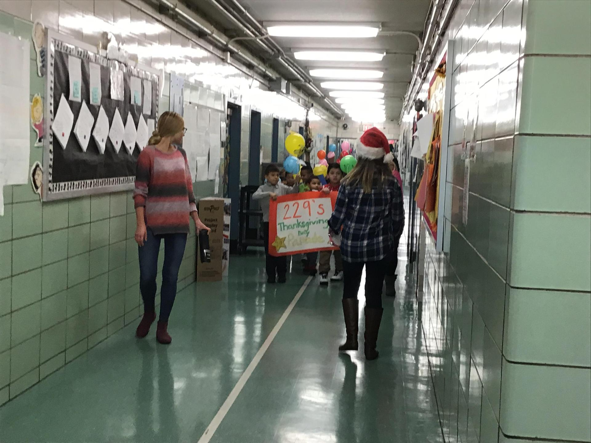 students parading in school hallway with balloons and teacher