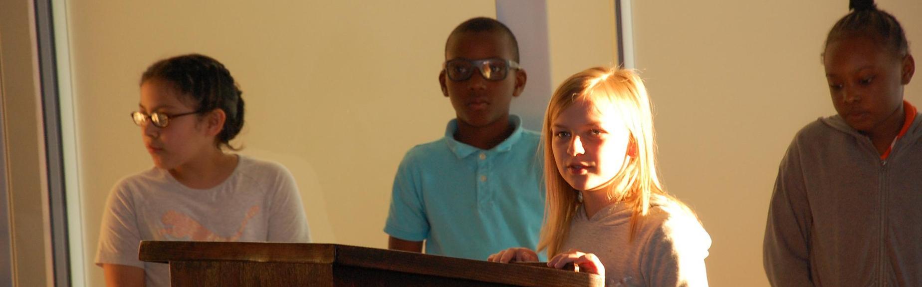 students standing at podium presenting at a board meeting