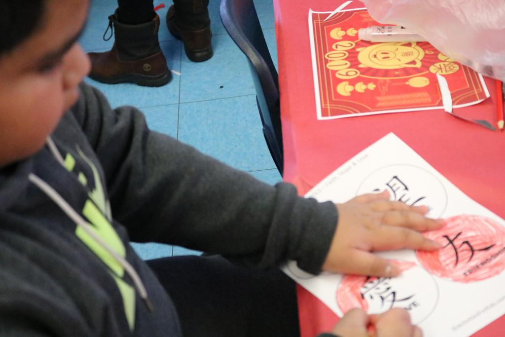 boy coloring chinese words in cirlce