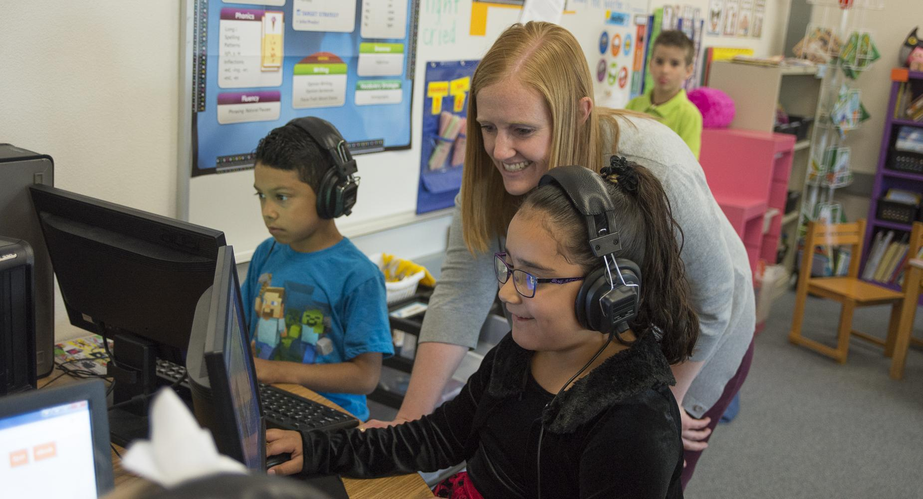Teacher assists students wearing headphones at the computer.