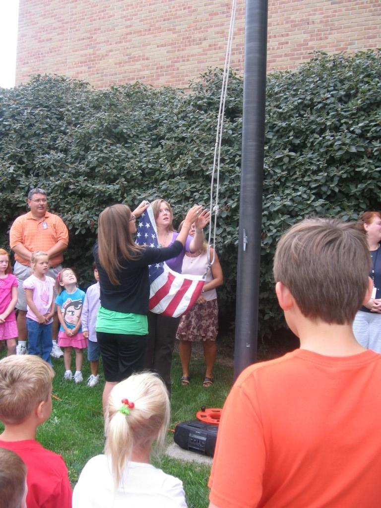 students raise American flag outside