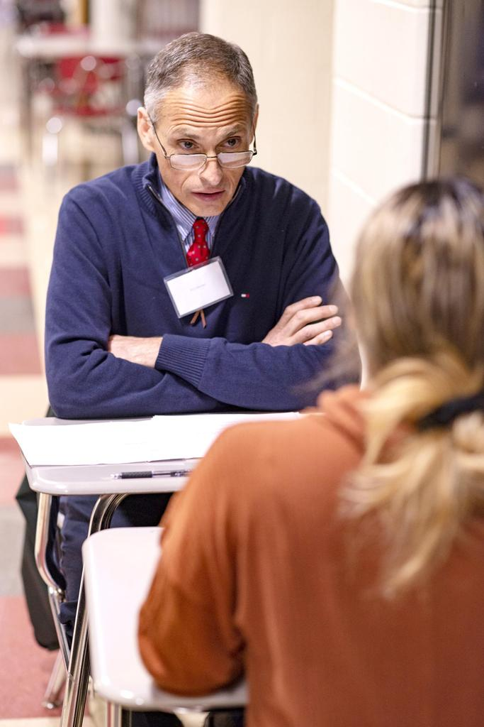 An interviewer looks across a table at a student