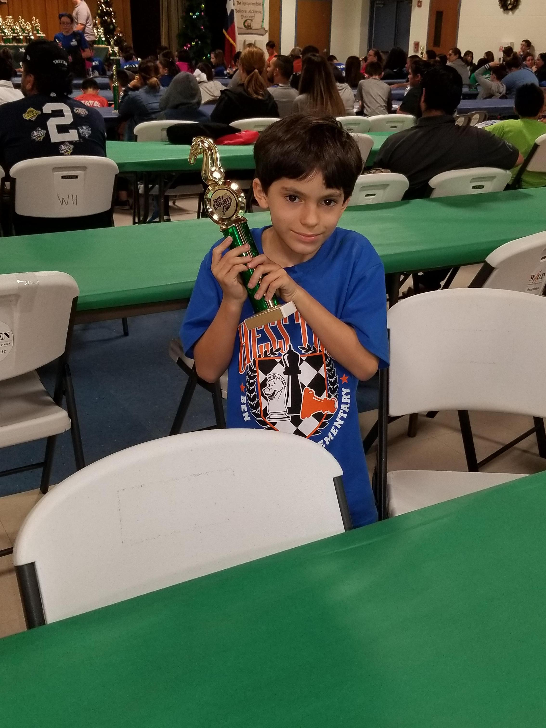 Student with chess trophy.