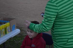 A student gets his face painted.