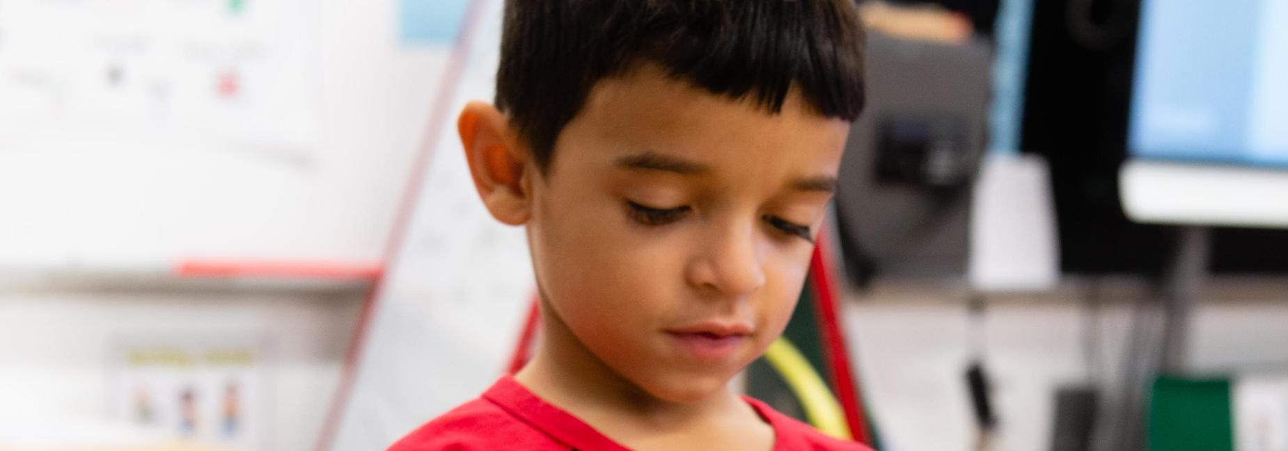 A pre-k student in a classroom looking down pensively.