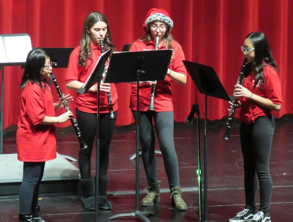 Four female clarinet players perform at center stage