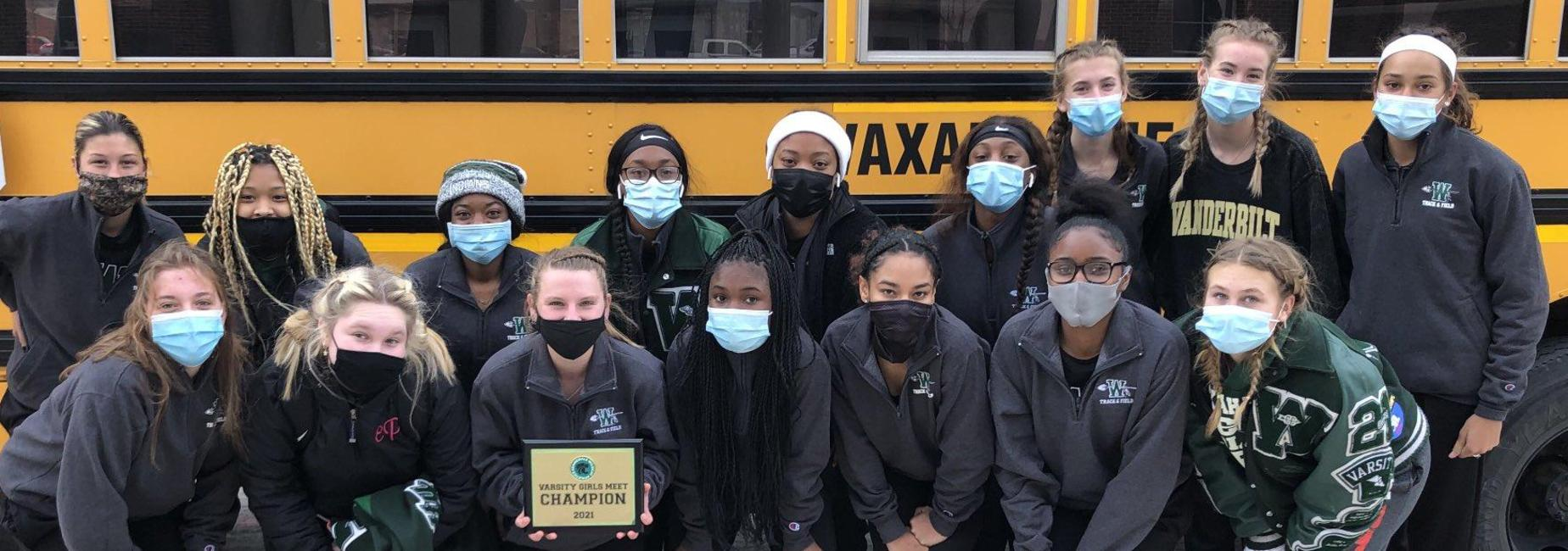 group of teen girls in face masks stand beside school bus