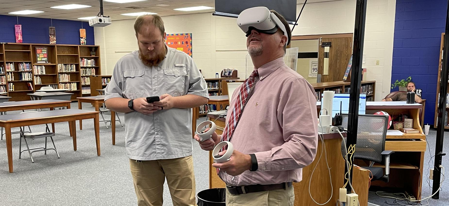 Two men use a virtual reality headset in a library.