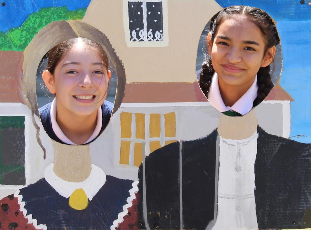 two students posing in front of cut out art board