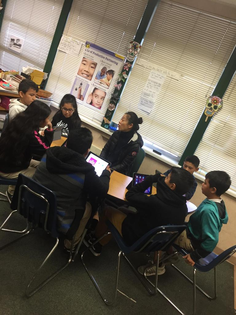 employee from Apple gathers at half moon table with students guiding them on coding