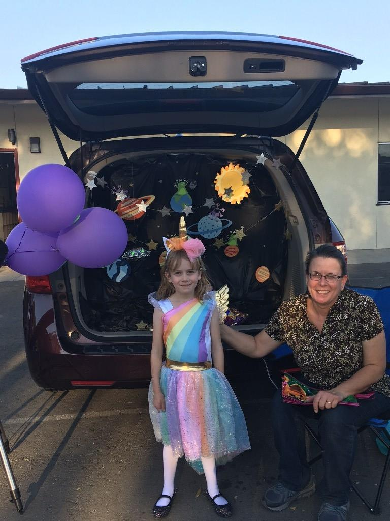 solar system decorated trunk with child dressed in unicorn costume