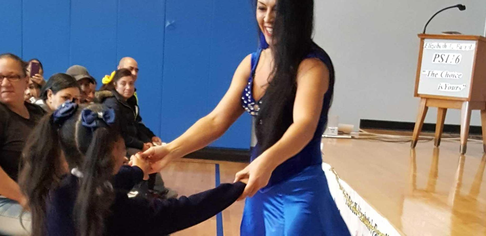 Flamenco Dancer, dances with a student at front of stage with parents looking on.