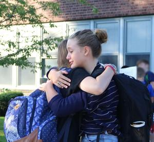 Two Edison Intermediate School students greet each other with a big hug on first day of school.