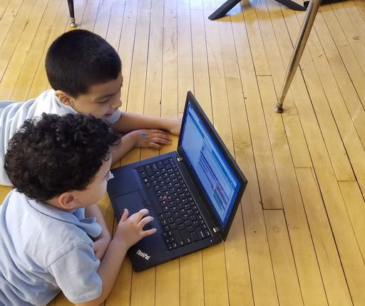 Two students lying on floor sharing a computer, working on coding task on CS4ALL 2019 Day.