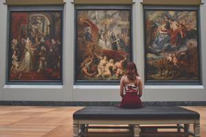 Photo of person at a museum sitting in front of a painting
