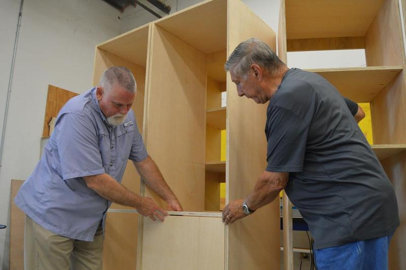 Golden Isles College and Career Academy construction pathway instructor Jeff Holland, left, talks with Golden Isles Veterans Village Initiative, Inc., board member John Bartosh about new shelving built last week for six tiny homes in the village, which will serve homeless veterans in Brunswick.