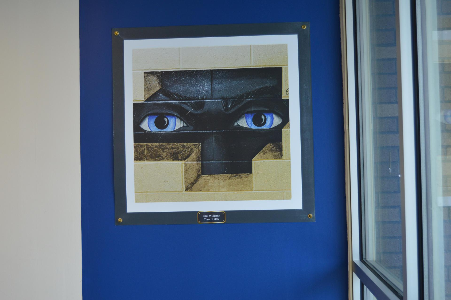Mural of a black face with large blue eyes looking through bricks on a wall