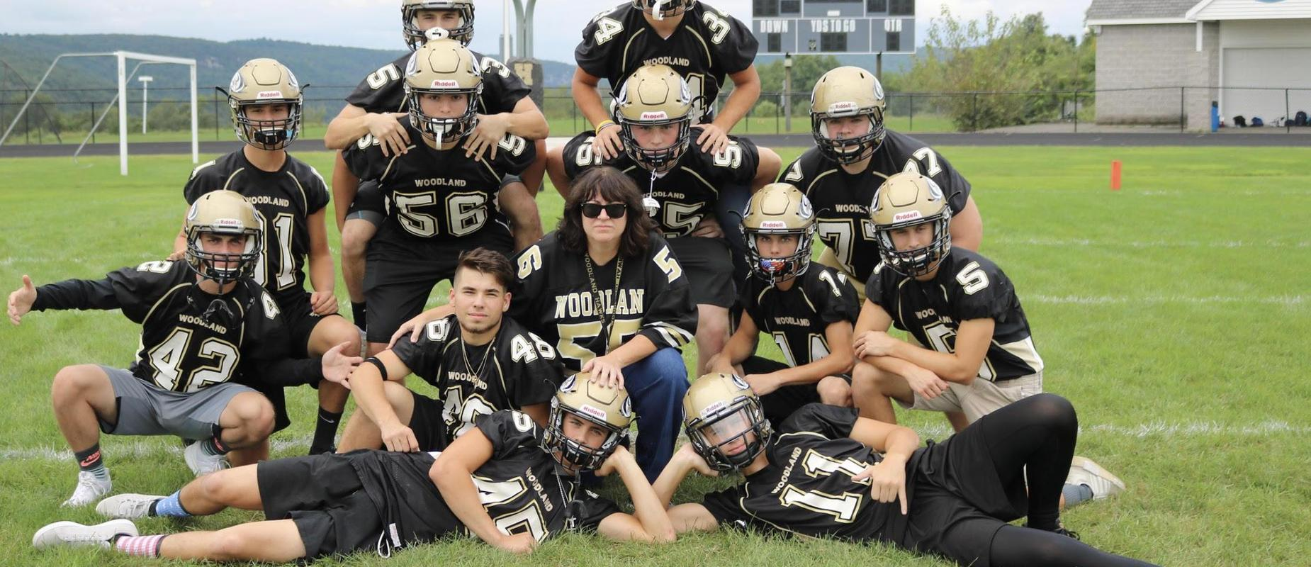 Image of teacher and football players