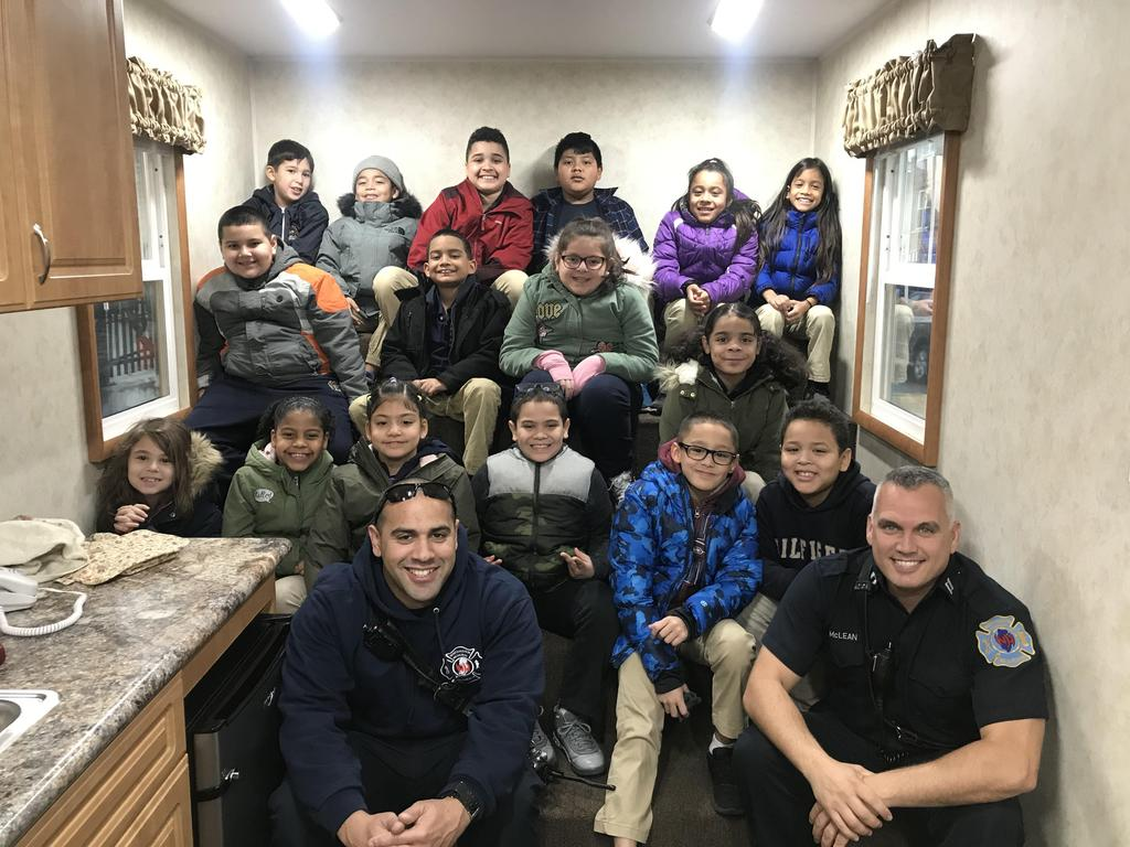 class poses with the two firefighters inside the fire safety house