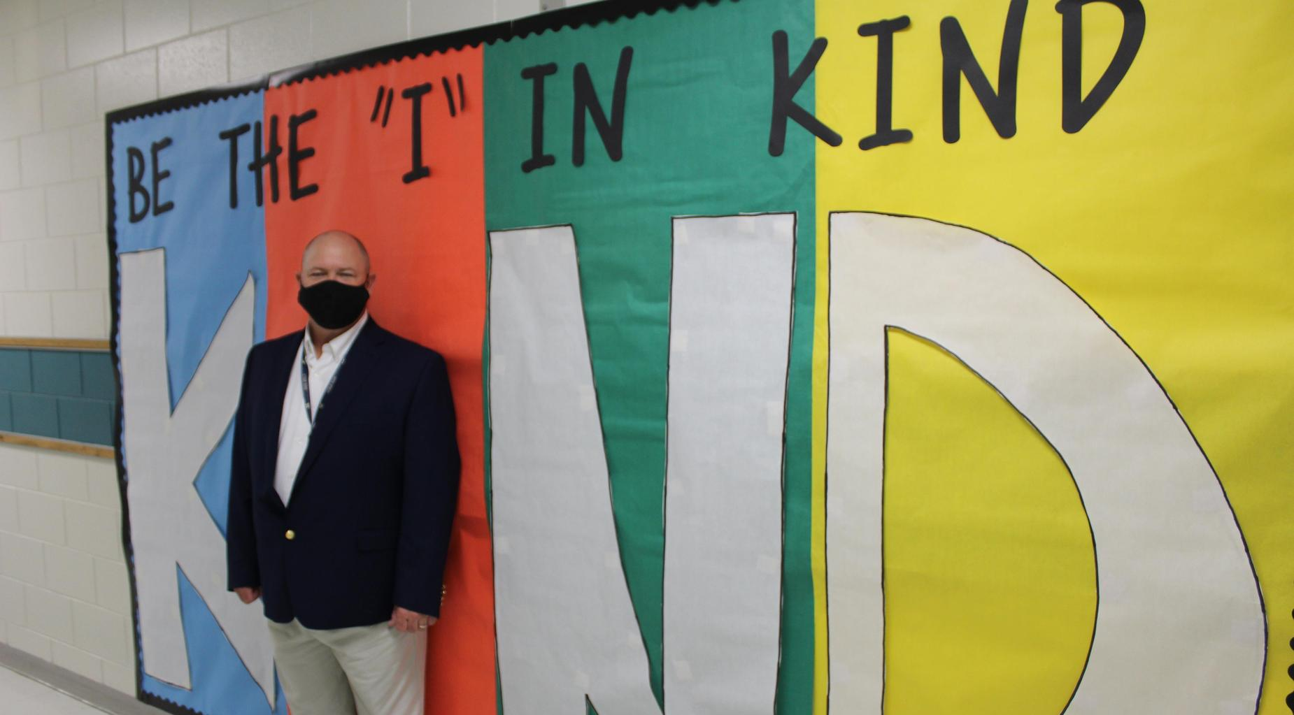 Dr. Scott Spence stands in front of a banner.