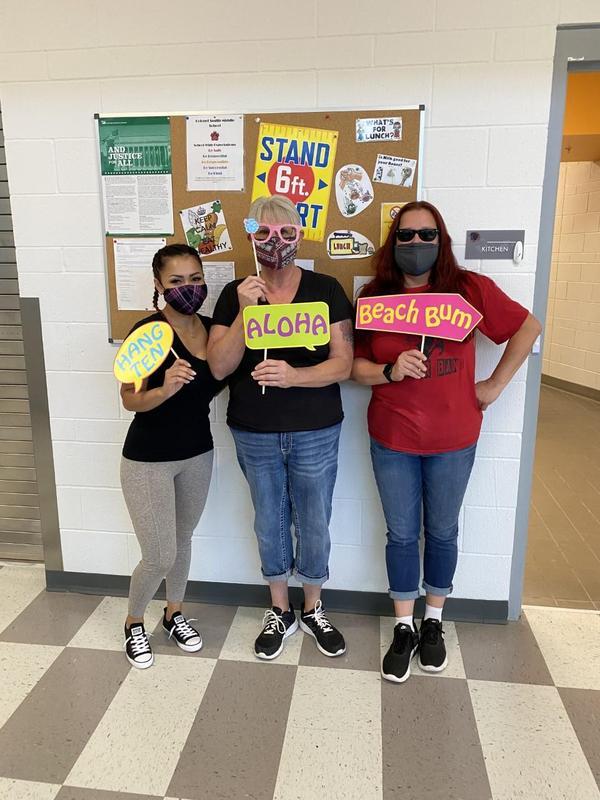 Three women posing with Hawaiian theme props