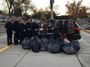 police officers and school administrators with bags full of donated coats
