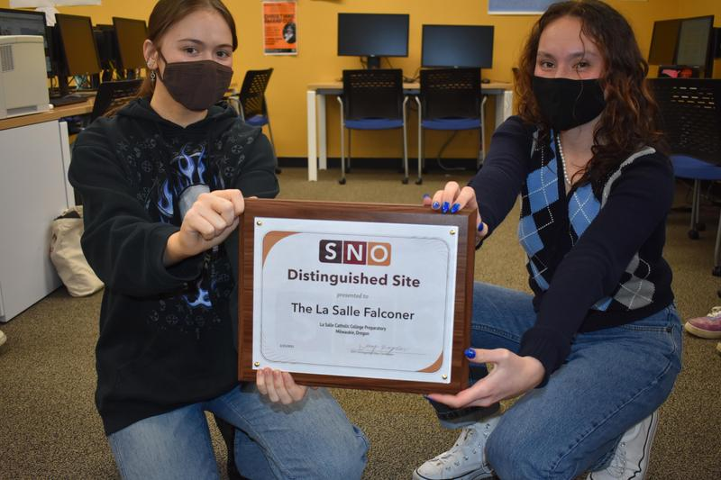 two girls holding plaque