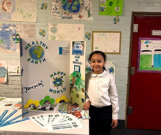 Student standing beside her Earth Day Project