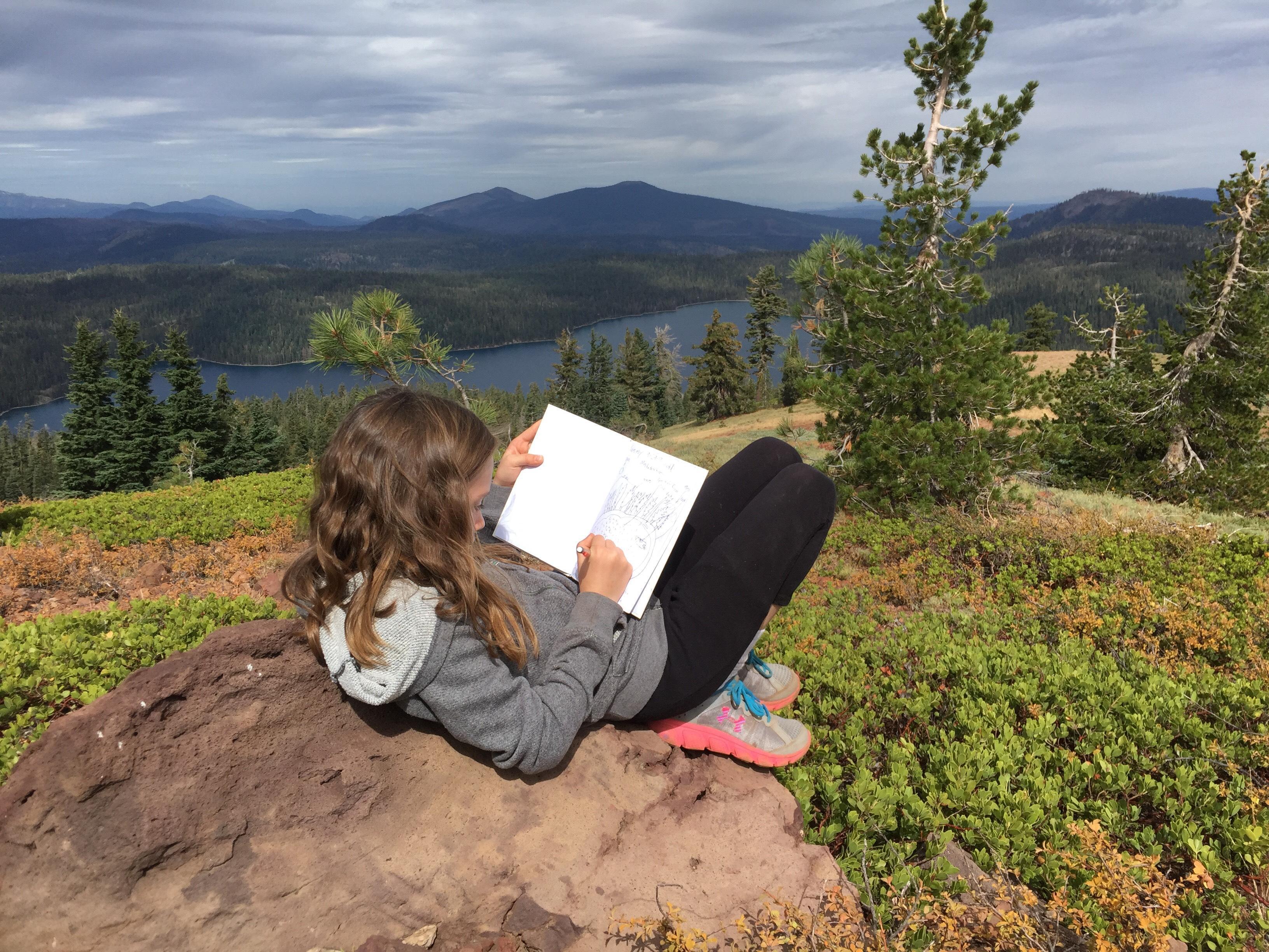 Child Reading on a Mountain