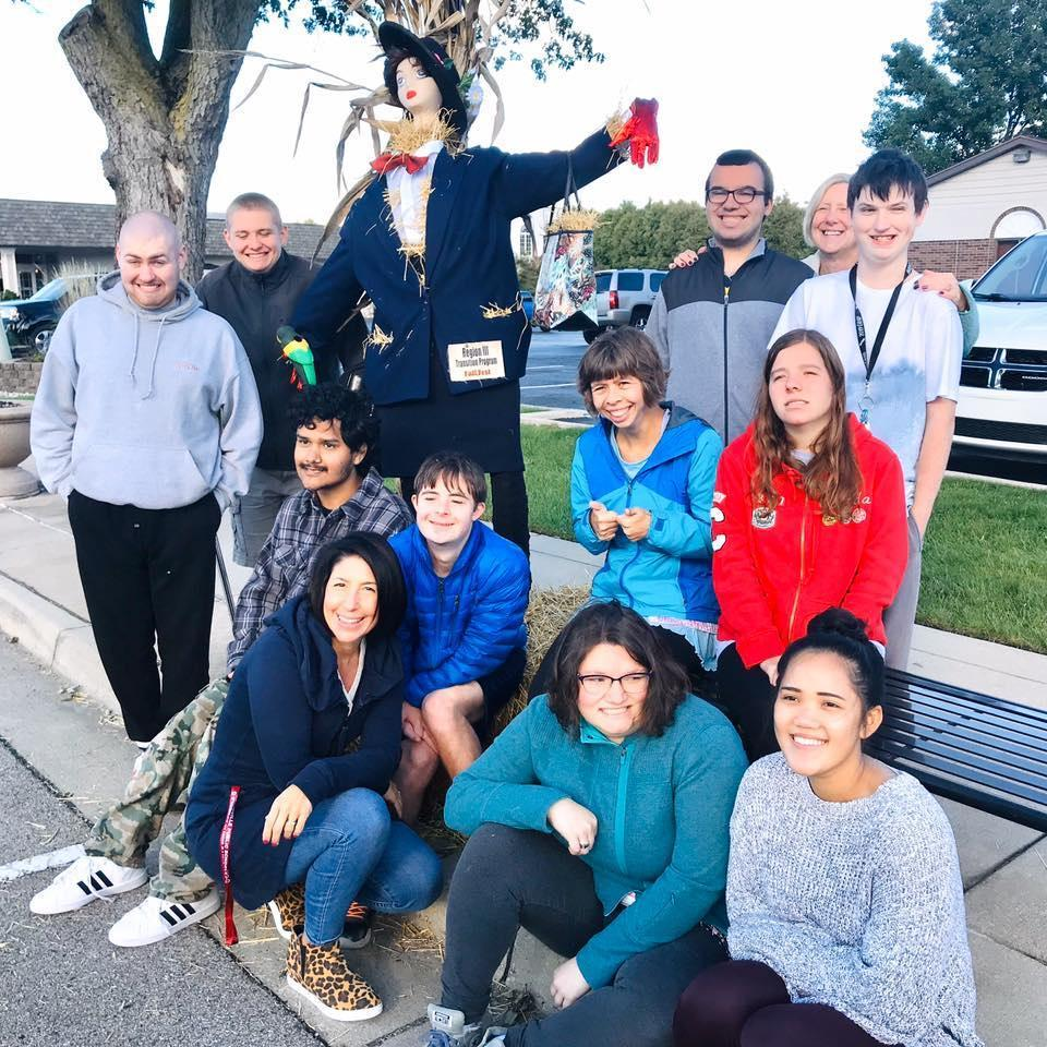 students stand by scarecrow they made on side of street