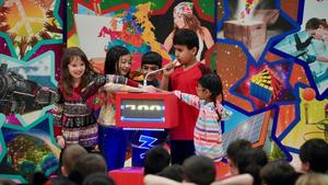 Four students holding down a buzzer during the Brain Show game show.