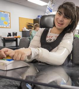 student using adaptive equipment to work on the school newspaper