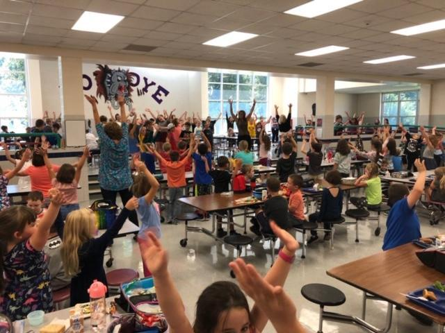 Mrs. Wright, elementary principal, leads all K-5 students in an impromptu dance party in the cafeteria to celebrate Friday and excellent Bulldog Four behavior by students.  Students are seen dancing and smiling.