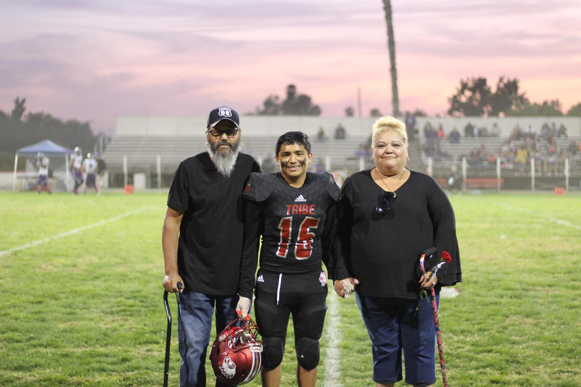 Senior football player Matthew Hernandez and his escorts.