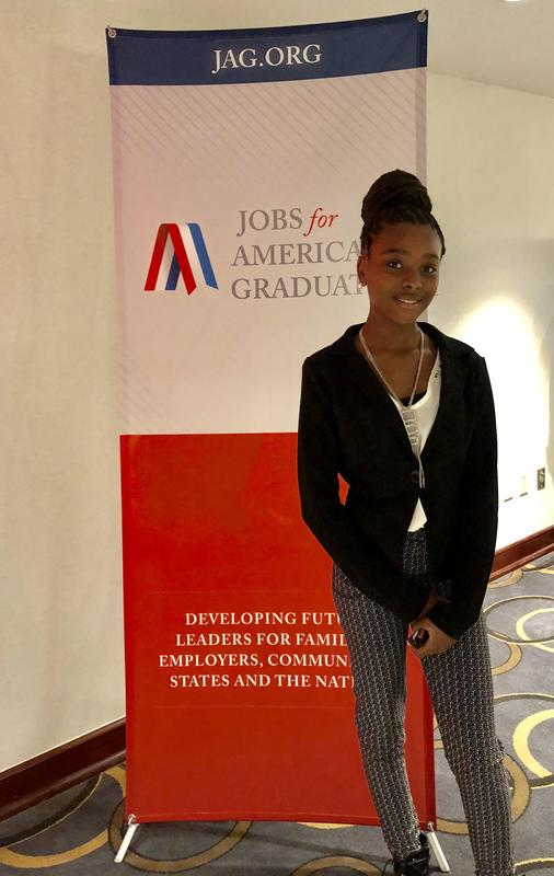 a photo of Baker Middle School JAG, Destiny Jones in front of the conference banner in hallway of the conference center.