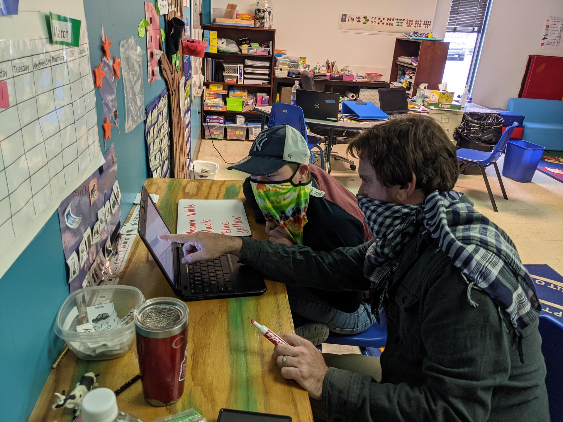 a student and teacher working at a computer