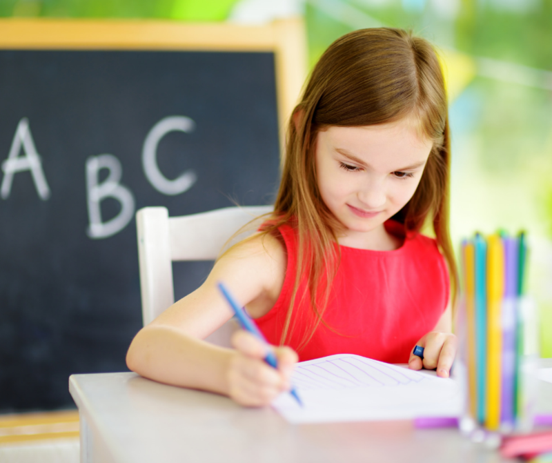 child writing with colored pencil and chalkboard behind her with ABC written on it