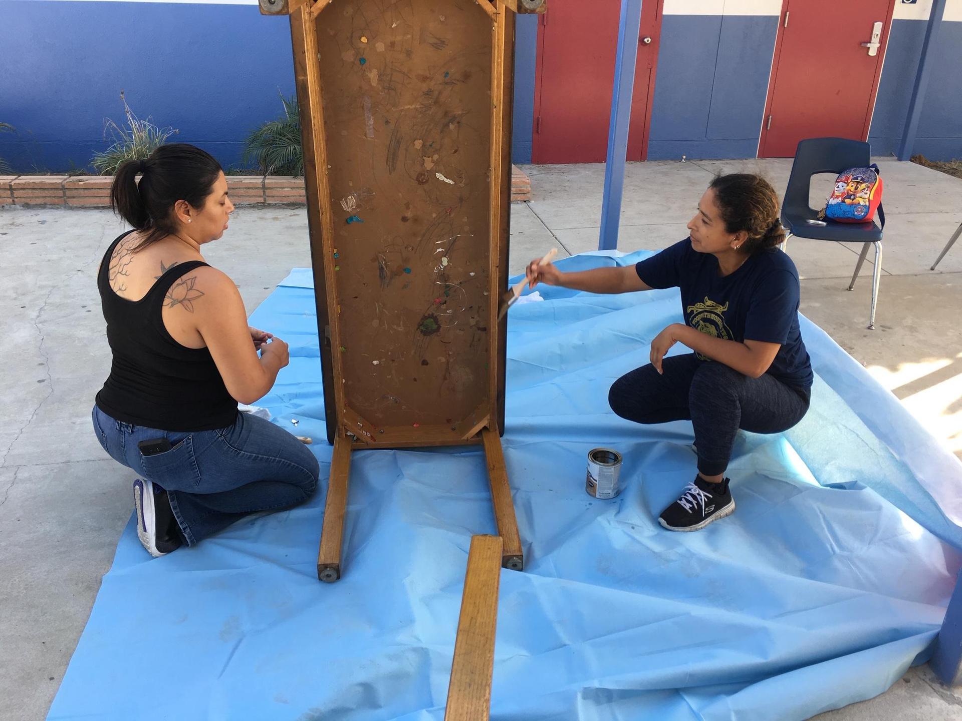 Parents sanding tables